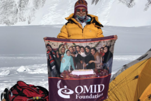 Sarah holding Omid Foundation banner in snow